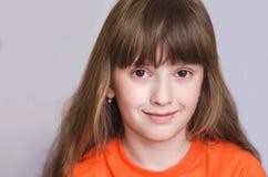 Das Mädchenlächeln und -blicke vorwärts Stockfoto