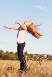 Das Mädchenwerfen gehen zurück im Wind voran stockbilder