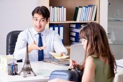 Das männliche Reisebüro mit Kunden in der Agentur Lizenzfreie Stockfotos