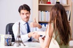Das männliche Reisebüro mit Kunden in der Agentur Stockbild