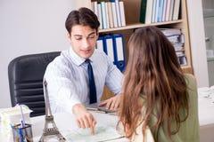 Das männliche Reisebüro mit Kunden in der Agentur Stockfotografie