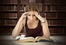 Das müde Studentmädchen, das für Hochschulprüfung studiert, sorgte sich überwältigt Lizenzfreie Stockfotografie