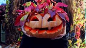 Das M?dchen h?lt einen geschnitzten K?rbis, von dem die roten Bl?tter hervorstehen Halloween-K?rbissymbol stock video footage
