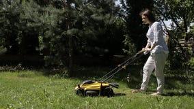 Das M?dchen m?ht einen ungleichen Rasen mit gelbem Rasenm?her barfu? stock footage