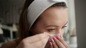Das M?dchen nahe dem Spiegel leitet Sch?nheitsbehandlungen auf dem Gesicht Das M?dchen setzt Flecken auf den Bereich unter die Au stock video
