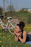 Das M?dchen steht auf der Fr?hlingswiese still L?gen auf der Bettdecke Ist in der N?he ein Fahrrad L?wenzahn bl?ht, junges Gras w lizenzfreie stockfotos