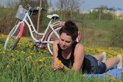Das M?dchen steht auf der Fr?hlingswiese still L?gen auf der Bettdecke Ist in der N?he ein Fahrrad L?wenzahn bl?ht, junges Gras w stockfotografie