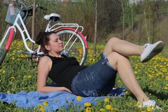 Das M?dchen steht auf der Fr?hlingswiese still L?gen auf der Bettdecke Ist in der N?he ein Fahrrad L?wenzahn bl?ht, junges Gras w stockfoto