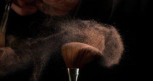 Das Make-upbürstenverbreiten erröten Pulver auf schwarzem Hintergrund, Zeitlupe stock video