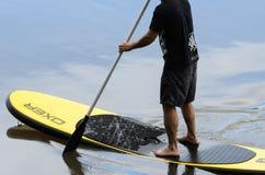 Das Mannüben stehen oben Paddel im Wasser von See IgapÃ-³ Lizenzfreie Stockbilder