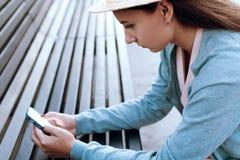 Das Mädchen betrachtet das Telefon auf der Straße Lizenzfreie Stockfotos
