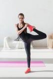 Das Mädchen, das arbeitet, Bein ausdehnend mit, mischt Aufwärmen an Stockfoto