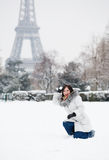 Das Mädchen, das Schneebälle spielt, nähern sich dem Eiffelturm in Paris Lizenzfreies Stockfoto