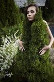 Das Mädchen in einem Kleid von einem dekorativen Pelzbaum. Stockfotografie