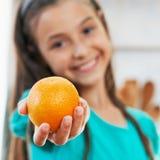 Das Mädchen hält die Orange an Stockbilder