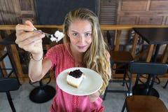 Das Mädchen isst Kuchen, das kühle Mädchen mit Kuchen Lizenzfreies Stockbild