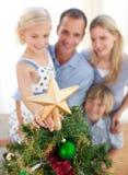 Das Mädchen setzte den Weihnachtsstern oben auf den Baum Lizenzfreie Stockfotografie