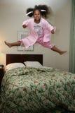 Das Mädchen springend auf Bett Stockbild