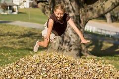 Das Mädchen springend in Blatt-Stapel Stockbild