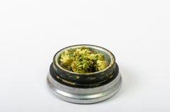 Das medizinische Marihuana, das oben gerieben wird und bereiten vor, um zu rollen Mit einem Stahlknospenkerl stockfoto