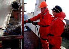 Das Meer von Japan/von Russland - 1. Dezember 2013: Säubern des Netzes des epibenthic Schlittens mit dem Wasserschlauch lizenzfreie stockbilder