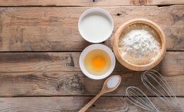 Das Mehl in einer hölzernen Schüssel, in einem Ei, in einer Milch und in einer Peitsche für das Schlagen Lizenzfreies Stockfoto