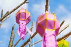 Das Mehrfarben der Lanna-Gebets-Laternendekoration auf einem Baum in den Zeremonien an einem buddhistischen Tempel stockfotografie