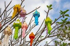 Das Mehrfarben der Lanna-Gebets-Laternendekoration auf einem Baum in den Zeremonien an einem buddhistischen Tempel stockbilder