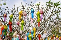 Das Mehrfarben der Lanna-Gebets-Laternendekoration auf einem Baum in den Zeremonien an einem buddhistischen Tempel stockbild