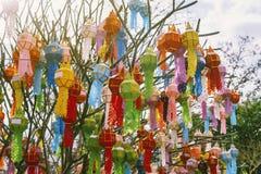 Das Mehrfarben der Lanna-Gebets-Laternendekoration auf einem Baum in den Zeremonien an einem buddhistischen Tempel stockfotos