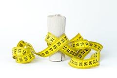 Das messende Band, das um eine Rolle des Toilettenpapiers eingewickelt wird, nähren Konzept Lizenzfreie Stockfotos