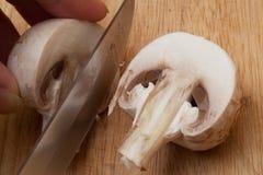 Das Messer schneidet den Agaricus stockbilder