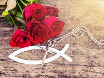 Das Metallkreuz mit roten Rosen auf Holztisch Lizenzfreies Stockbild