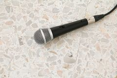 Das Mikrofon, das auf Bodenmarmor dynamisch ist, polierte Steinhintergrund stockbild