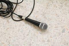 Das Mikrofon, das auf Bodenmarmor dynamisch ist, polierte Steinhintergrund stockfoto