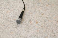 Das Mikrofon, das auf Bodenmarmor dynamisch ist, polierte Steinhintergrund stockfotos