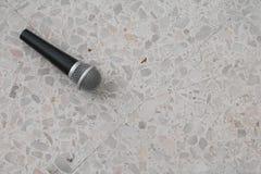 Das Mikrofon, das auf Bodenmarmor dynamisch ist, polierte Steinhintergrund lizenzfreies stockbild