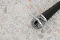 Das Mikrofon, das auf Bodenmarmor dynamisch ist, polierte Steinhintergrund lizenzfreie stockbilder