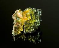 Das Mineralwismut auf einer schwarzen reflektierenden Oberfläche Stockfotos
