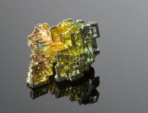 Das Mineralwismut auf einer schwarzen reflektierenden Oberfläche Stockfoto