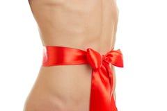 Das Mittelteil eines jungen Mädchens mit geknotetem Bogen auf ihm vom roten Band Lizenzfreie Stockfotos