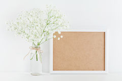 Das Modell des Bilderrahmens verziert blüht im Vase auf weißem Arbeitsschreibtisch mit sauberem Raum für Text und entwirft Ihr bl Lizenzfreies Stockbild