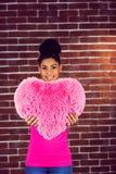 Das Modell des schwarzen Haares des Porträts, das ein rosa Herz hält, formte Kissen Stockfotografie