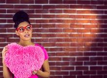 Das Modell des schwarzen Haares des Porträts, das ein rosa Herz hält, formte Kissen Stockbilder