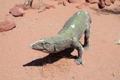 Das Modell eines Dinosauriers im Sand Lizenzfreies Stockfoto