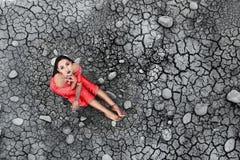 Das Modell sitzt auf dem getrockneten Boden Lizenzfreies Stockfoto