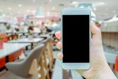 Das Modellbild der Hand weißes Mobiltelefon mit leerem schwarzem Schirm halten, der, Bildcafé zu nehmen im Einkaufszentrum ist, w stockfoto