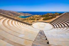 Das moderne Amphitheater, welches das Ägäische Meer übersehen und Milopotas setzen auf die Kykladen-Insel von IOS auf den Strand lizenzfreies stockbild