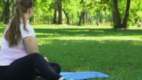 Das mollige Mädchen, das mit nettem Hund während des Yogatrainings spielt, brechen, Erholung stock footage