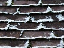 Das Moos zwischen den Ziegelsteinen besprühte das weiße Schneelabyrinth Lizenzfreies Stockfoto